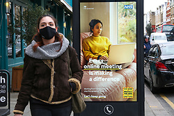 © Licensed to London News Pictures. 26/03/2021. London, UK. A woman wearing a protective face covering walks past the government's 'Every online meeting is making a difference' poster in north London as MPs voted to extended emergency Covid-19 powers for another 6 months. The next key date for restrictions easing is Monday 29 March 2021, when the 'Stay at Home' guidance will be dropped. Photo credit: Dinendra Haria/LNP