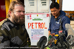 Tattoo artist Justin Big Meas Wilson gets his Royal Enfield Himalayan filled up on Motorcycle Sherpa's Ride to the Heavens motorcycle adventure in the Himalayas of Nepal. Riding from Pokhara to the National Park in Chitwan, Monday, November 11, 2019. Photography ©2019 Michael Lichter.