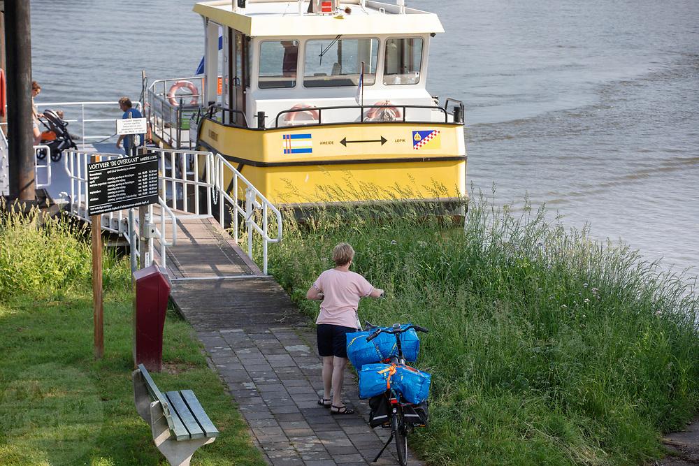 Fietsers nemen bij Ameide het voetveer over de Lek tussen Lopik en Ameide.<br /> <br /> Cyclist take a ferry between Ameide and Lopik.