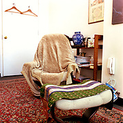 A white fabric covered Stressless chair and footrest in a small white room. There is a beige throw hanging aimlessly over the chair and a green, white, and purple patterned fabric across the footrest, a red patterned Oriental rug on the dark wooden floor, and a wooden collapsable bookshelf to the right and behnind the chair. The door is in the background, two wooden hangers on hooks near the top of the frame. There is also a white phone on the wall above a blue patterned plastic bag, just to the right of the footrest and chair.