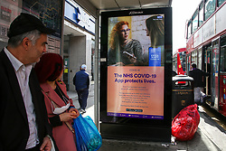 © Licensed to London News Pictures. 09/09/2021. London, UK. People look at the government's 'The NHS COVID-19 App protects lives' latest advertising campaign poster displayed at a bus stop in north London as coronavirus infection cases continue to rise. As at 8 September, the UK recorded just under 39,000 new infections, an increase of 15.3% compared to the week before. Photo credit: Dinendra Haria/LNP