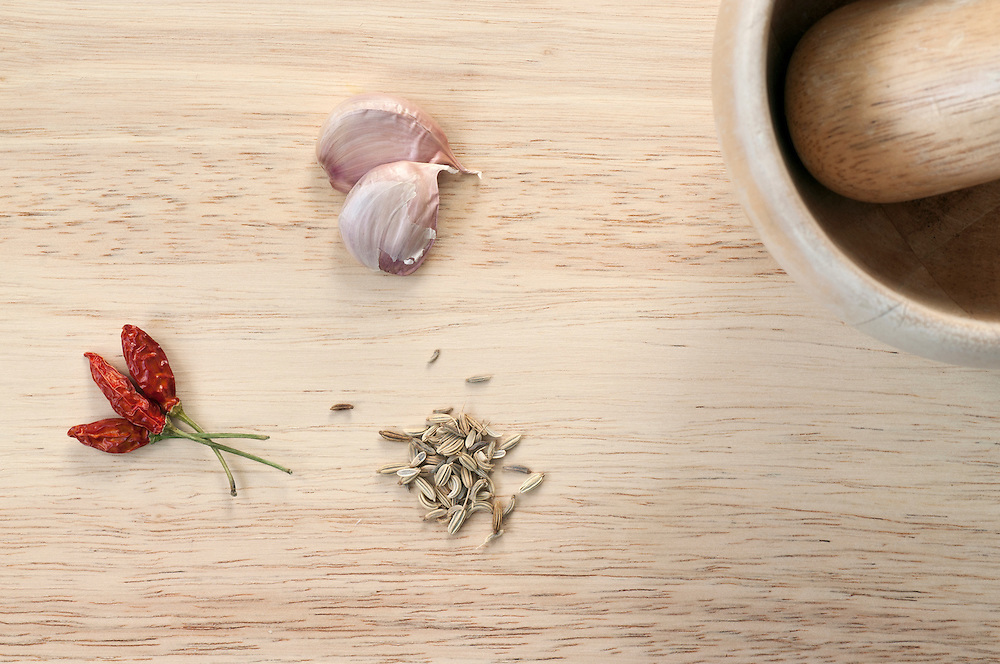 Chopping board containing garlic, red chilli & fennel seeds.