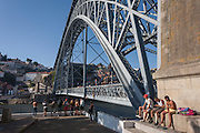 Local youths sunbathe while others are about to dive off the Ponte de Dom Luis I bridge with the city of Porto behind on the River Douro, on 20th July, in Porto, Portugal. For the price of a Euro, will the boys leap off the girders, into the cold water - known as tombstoning, due to its obvious dangers. The Dom Luís I (or Luiz I) Bridge is a double-decked metal arch bridge that spans the Douro River between the cities of Porto and Vila Nova de Gaia in Portugal. At the time of construction its span of 172 m was the longest of its type in the world. (Photo by Richard Baker / In Pictures via Getty Images)
