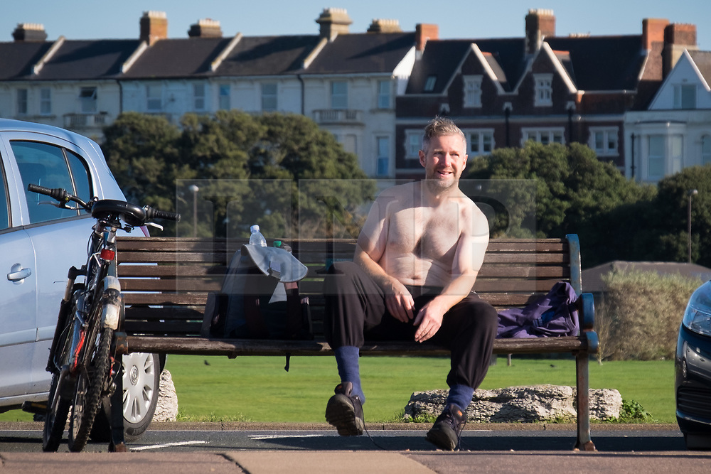 © Licensed to London News Pictures. 27/10/2017. Portsmouth, UK.  A topless man sat on a bench making the most of the sunny weather on Southsea promenade today, 27th October 2017.  Photo credit: Rob Arnold/LNP