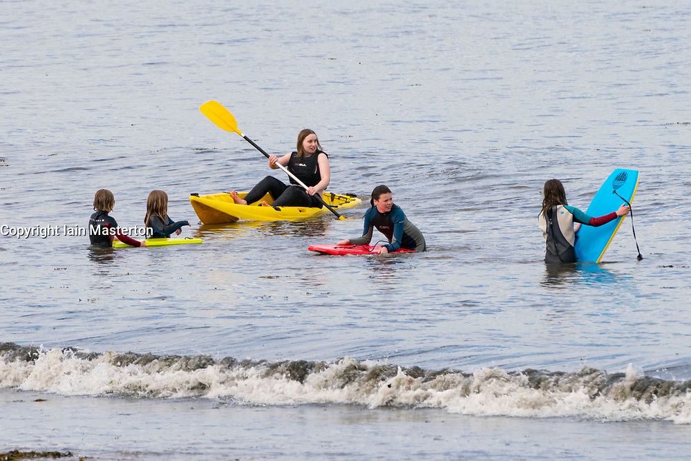 Portobello, Scotland, UK. 11 May 2020. Late afternoon views of popular Portobello beach and promenade. Despite occasional police patrols, the public were determined to relax and enjoy sitting in the sunshine. Family enjoying the sea with canoes and surfboards. Iain Masterton/Alamy Live News