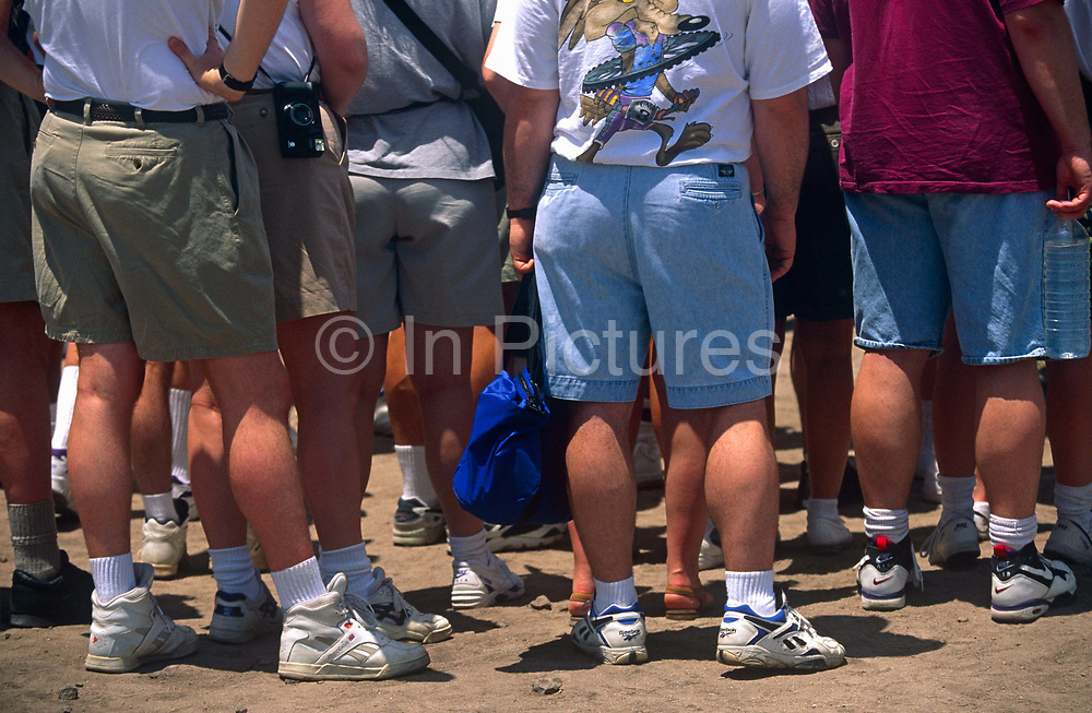 From the wastes down, we look at the legs and posteriors of rather overweight tourists who stand in tropical heat to listen as a tour guide tells them about the Mayan pyramids that they have driven to see, during a Carnival cruise ship voyage from Miami to Cancun. Wearing the same style Reebok and Nike trainers and similar white sports socks and long shorts, their calves are thick and their bottoms are wide but they all stand motionless to hear the cultural and historical detail of this ancient place.