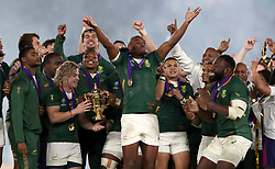 South Africa's Makazole Mapimpi (centre) celebrates as Faf de Klerk holds the Webb Ellis cup with Siya Kolisi (hidden) after South Africa win the 2019 Rugby World Cup final match at Yokohama Stadium.