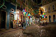 Two 2 men arm in arm gay couple, young 20's 30's Brazilian, at night with colourful lighting in the historic centre of Salvador da Bahia, Pelourinho, Bahia, Brazil.