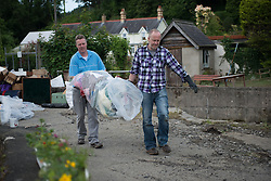© Licensed to London News Pictures. 11/06/2012. Cereredigion, UK. Residents of Dolybont, Cereredigion, clean up after the flash floods of Saturday 9 June. Over 5 inches of rain fell on already saturated ground on the friday, leading to huge surges of water down the Leri River into the village. . Photo credit : Keith Morris/LNP