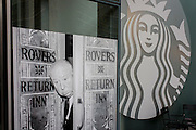 Photograph of film director Alfred Hitchcock on the Coronation Street TV soap set alongside the modern Starbucks logo.