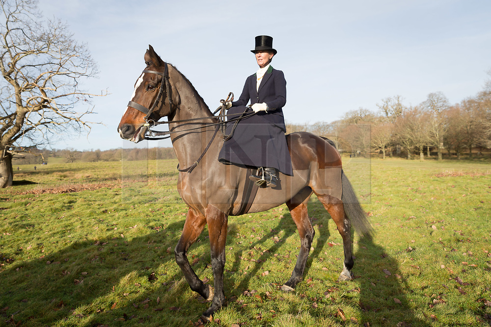 © Licensed to London News Pictures. 26/12/2017. Petworth, UK. A woman wearing traditional costume arrives riding side saddle at the Chiddingfold, Leconfield and Cowdray Boxing Day hunt which starts at Petworth House to large crowds of supporters. Photo credit: Vickie Flores/LNP
