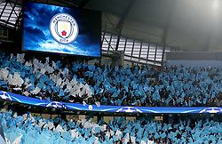 Manchester City fans wave flags in the stands to show their support