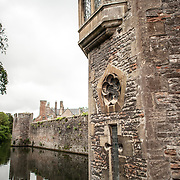 A defensive tower and moat around the Bishop 's Palace in Wells, Somerset, England.