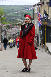 © Licensed to London News Pictures. 13/05/2016. Haworth, UK.  Kirsty Garwood, wearing 1940s attire, poses on the bunting draped street during the annual 1940's weekend in Haworth, West Yorkshire.  Photo credit : Ian Hinchliffe/LNP