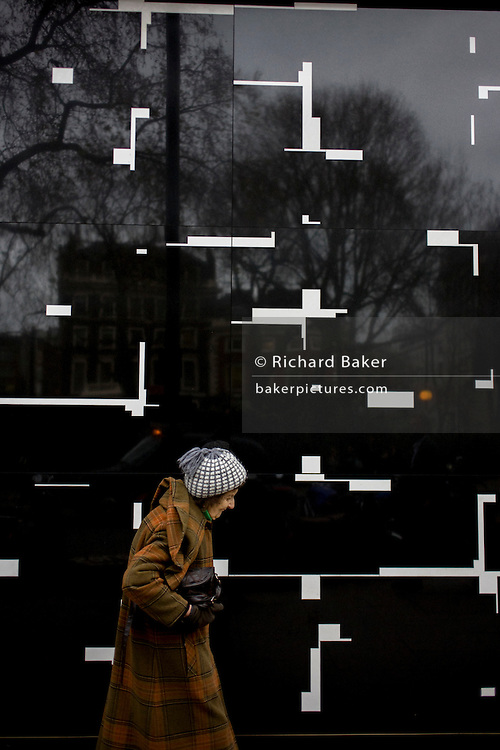 Elderly lady with a background of a geometric-designed wall in central London