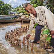 CAPTION: Mai Van Cho showing an erosion barrier that he is in the process of constructing close to his house. LOCATION: An Binh Ward, Can Tho, Vietnam. INDIVIDUAL(S) PHOTOGRAPHED: Mai Can Cho.