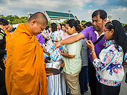 01 JANUARY 2016 - BANGKOK, THAILAND:         People make merit by presenting Buddhist monks with alms during the annual New Year's mass merit making ceremony on at Sanam Luang in Bangkok. The ceremony is sponsored by the Bangkok city government. More than 500 Buddhist monks participated in the ceremony this year. Thais usually go to temples and religious observances to meditate and make merit on New Year's Day.    PHOTO BY JACK KURTZ