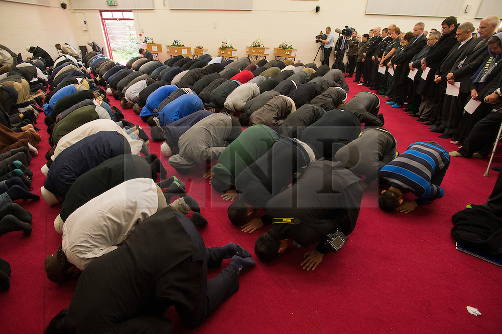 © London News Pictures. 24/10/2012. Harlow, UK. Members of the local Muslim community praying and members of the emergency services in front of the six coffins during the funeral service of Dr Sabah Usmani and her five children Hira (12), Sohaib (11) Muneeb (9), Rayyan (6) and Maheen (3) at Harlow Islamic Centre in Harlow, Essex, UK on October 24, 2012. Dr Sabah Usmani and her five children died blaze at their home in Harlow last week. Photo credit: Ben Cawthra/LNP