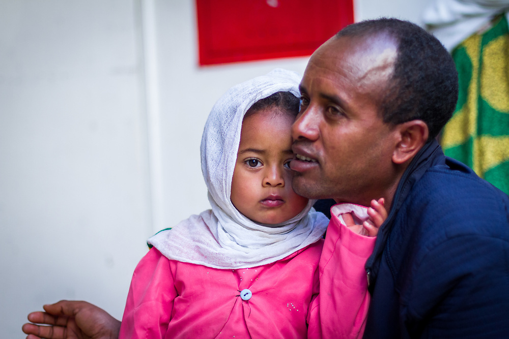 INDIVIDUAL(S) PHOTOGRAPHED: Assaye Haile Leoul (left) and Atsede Mariam Assaye (right). LOCATION: Mecha Health Center, Bahir Dar, Ethiopia. CAPTION: Child patient Atsede Mariam Assaye, and her father Assaye Haile Leoul, share an intimate moment as they wait in line to be seen.
