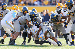 Sep 11, 2021; Morgantown, West Virginia, USA; Many West Virginia Mountaineers defenders tackle Long Island Sharks running back Jonathan DeBique (2) during the first quarter at Mountaineer Field at Milan Puskar Stadium. Mandatory Credit: Ben Queen-USA TODAY Sports