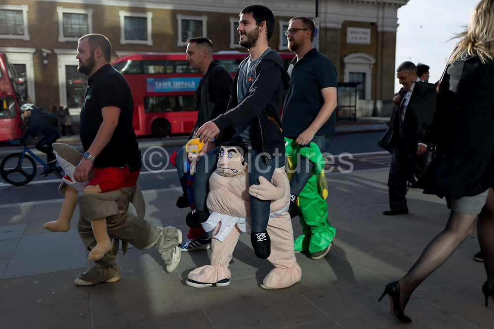 Men in fancy dress while commuters and other pedestrians walk over London Bridge, the oldest of the capitals crossing over the river Thames between the capitals financial district, the City of London, and Southwark on the south bank, on 17th May 2018, in London, UK.