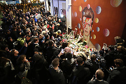 © Licensed to London News Pictures. 11/01/2016. London, UK. People gather round a mural of David Bowie in Brixton. The Death of David Bowie, who was born in Brixton, has been announced today.  Photo credit: Peter Macdiarmid/LNP