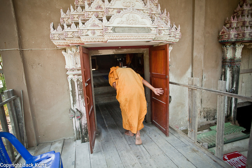 Apr. 3, 2010 - KHUN SAMUTCHINE, THAILAND: Abbot ATHIKARN SOMNUK ATIPANYO, at Wat Samutchine, ducks to enter the prayer hall at the temple. Members of the temple raised the floor inside the temple by about six meet so they could continue to use it. The lower half of the temple is completely underwater. Rising sea levels brought about by global climate change threaten the future of Khun Samutchine, a tiny fishing village about 90 minutes from Bangkok on the Gulf of Siam. The coastline advances inland here by about 20 metres (65 feet) per year causing families to move and threatening the viability of the village. The only structure in the village that hasn't moved, their Buddhist temple, is completely surrounded by water and more than 2 kilometers from the village. The temple and the village have asked the Thai government and several NGOs for help, but the only help so far is a narrow concrete causeway the government is building that will allow people to walk into the temple from a boat landing two miles away. The walk to the village from a closer boat landing is shorter, but over an unimproved mud flat that is nearly impassible in the rainy season.  PHOTO BY JACK KURTZ