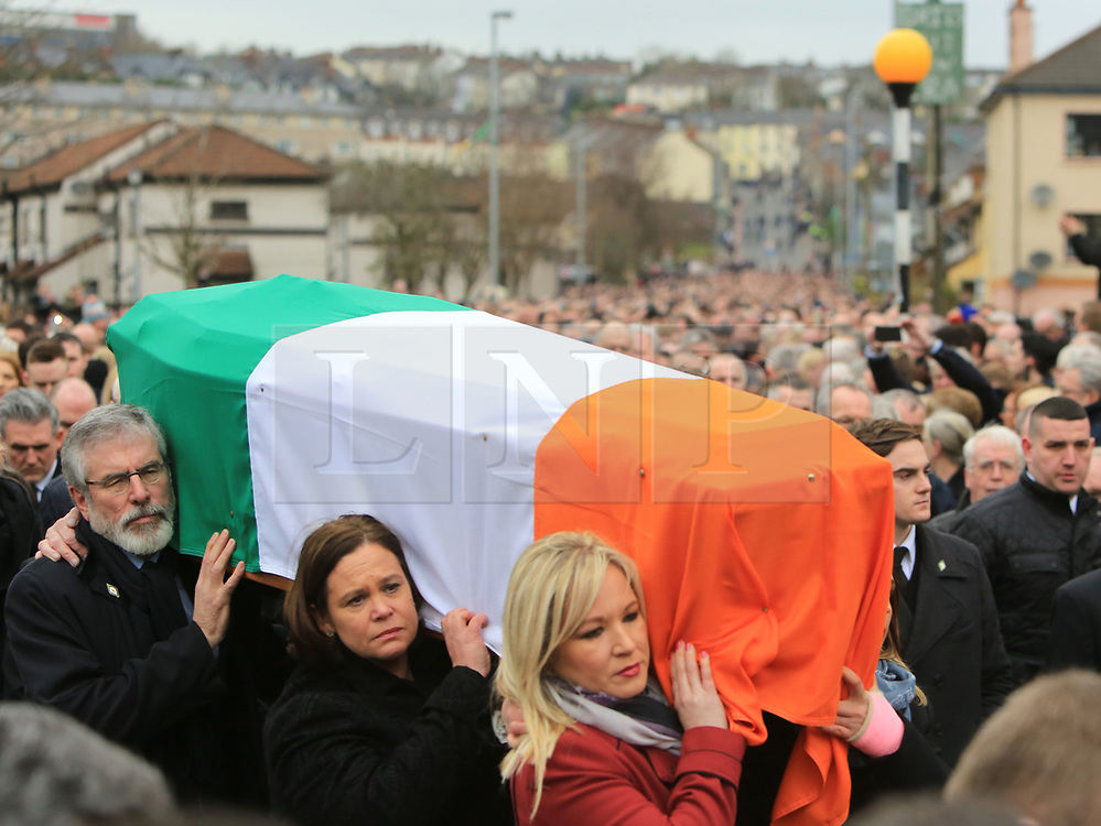 © Licensed to London News Pictures. 23/03/2017. Londonderry, UK. Gerry Adams, President of the Sinn Féin (L) carries the coffin of Martin McGuinness along with Mary Lou McDonald (C), Deputy Leader of Sinn  and Michelle O'Neill  (R) Northern Ireland Leader in Londonderry, Northern Ireland 23 March, 2017 during the funeral of Sinn Féin's Martin McGuinness. Mr McGuinness, a former IRA leader turned politician, died on Tuesday.. Photo credit: LNP