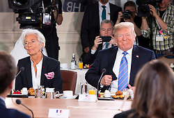 U.S. President Donald Trump, right, takes his seat after arriving late for the G7 and Gender Equality Advisory Council Breakfast, as IMF Managing Director Christine Lagarde looks on, left, at the G7 leaders summit in La Malbaie, Que., on Saturday, June 9, 2018. Photo by Justin Tang/CP/ABACAPRESS.COM