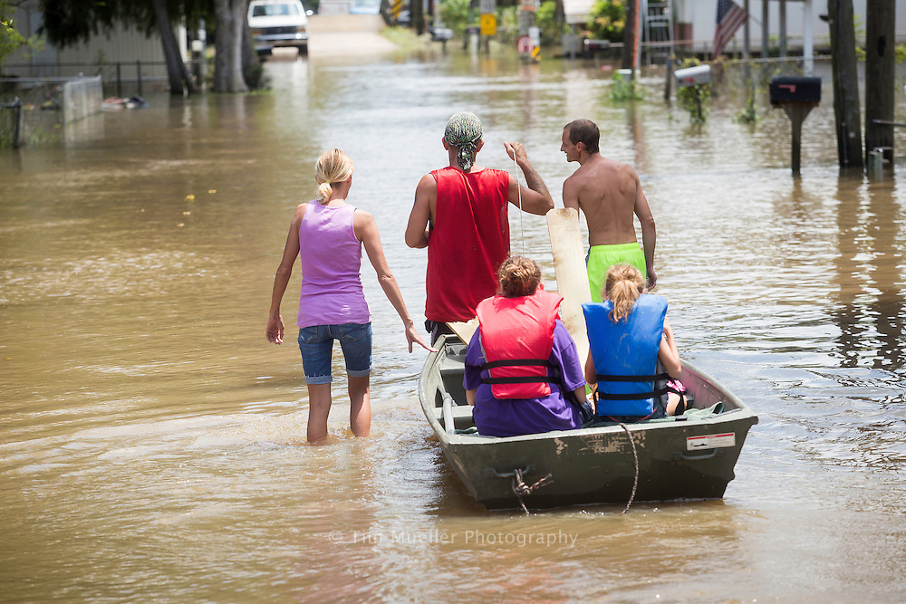 A father pulls his two children by boat Friday, August 19. 2016 to their home down Chinquapin Avenue off LA Hwy. 22 in south Livingston Parish. Although their home is elavated they still received several feet of flood water.