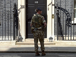 """A member of the army stands outside 10 Downing Street, London, after Scotland Yard announced armed troops will be deployed to guard """"key locations"""" such as Buckingham Palace, Downing Street, the Palace of Westminster and embassies."""