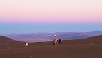 "Cyclist pushing his bike in the Atacama desert in the sunset, Chile (white ""stones"" indicates where ground water can be found)"