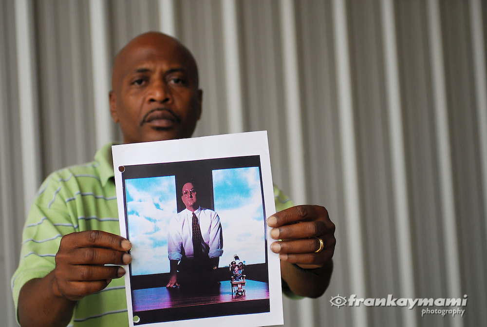 Photograph of John Thompson, who spent 14 of 18 years on death row for a crime he didn't commit, holds a photo of attorney Jim Williams that appeared in Esquire magazine. Williams is standing next to a miniature electric chair with photos of five men he sent to death row. Thompson's photo is in the center. New Orleans Photographer Frank Aymami