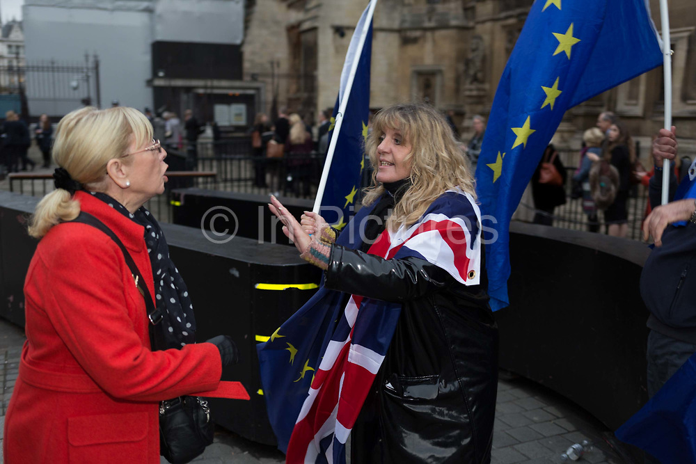 As MPs debate the timing of Brexit inside the House of Commons, a Brexiteer argues with a pro-Europe protester who holds EU and Union Jack flags outside Parlament, on 15th November 2017, in Westminster, London, England.