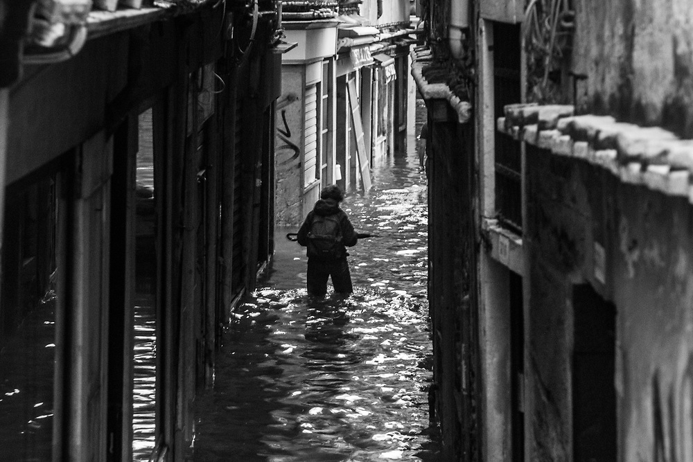Venice, Italy. 29 October, 2018. A woman walk through a flooded small street on October 29, 2018, in Venice, Italy. This is a selection of pictures of different areas of Venice that the press has not covered, were resident live and every year they have to struggle with the high tide. Due to the exceptional level of the 'acqua alta' or 'High Tide' that reached 156 cm today, Venetian schools and hospitals were closed by the authorities, and citizens were advised against leaving their homes. This level of High Tide has been reached in 1979. © Simone Padovani / Awakening / Alamy Live News