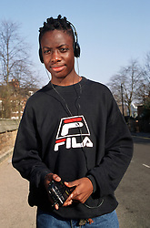 Teenage boy walking along street listening to personal stereo,