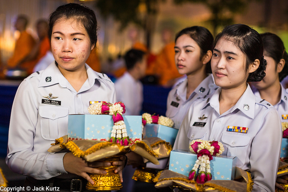 08 SEPTEMBER 2013 - BANGKOK, THAILAND: Women wait to present flower garlands to Buddhist monks at a mass alms giving ceremony in Bangkok. 10,000 Buddhist monks participated in a mass alms giving ceremony on Rajadamri Road in front of Central World shopping mall in Bangkok. The alms giving was to benefit disaster victims in Thailand and assist Buddhist temples in the insurgency wracked southern provinces of Thailand.      PHOTO BY JACK KURTZ