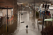 A man wades through flood waters in downtown Hoboken, New Jersey, Tuesday, October 30, 2012.  Photographer: Emile Wamsteker/Bloomberg News
