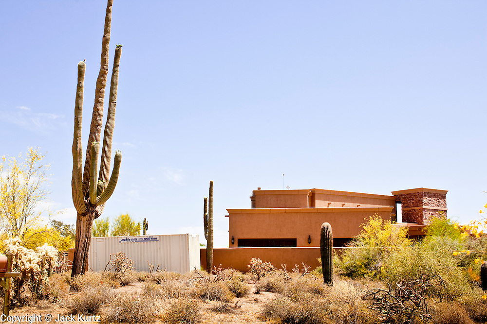 """22 MAY 2011 - SCOTTSDALE, AZ:  The desert surrounds a home reportedly owned by Sarah Palin in Scottsdale, AZ. According to the Arizona Republic, Sarah Palin and her husband Todd Palin, bought the 8,000 square foot home for $1.695 million cash. The newspaper said the Palin's name does not appear on the paperwork and the home was bought by Safari Investments LLC out of Delaware. The paper said the deal """"appears designed to cloak the identity of a high-profile buyer."""" The home has six bedrooms, five bathrooms, a six car garage, swimming pool, spa, home theater, wine cellar and children's """"jungle gym"""" in the backyard. The home is surrounded by a tall wall with an electronic gate. Phoenix TV stations have reported that a black SUV with Alaska license plates has been seen entering and leaving the compound. People in the house have refused to comment on who owns the home. Neither Palin nor her husband have been seen at the home since news of the sale broke Saturday, May 21.   Photo by Jack Kurtz"""