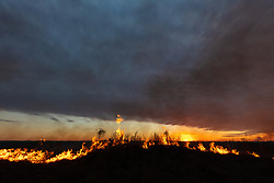 Flames and smoke in grasses at dusk during controlled burn on the Daphne Prairie, a remnant of the Blackland Prairie, Mount Vernon, Texas, USA.