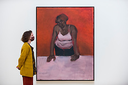 """© Licensed to London News Pictures. 02/12/2020. LONDON, UK. A staff member views """"Geranium Love Sonnet"""", 2010. Preview of """"Lynette Yiadom-Boakye: Fly In League With The Night"""" the first major UK survey exhibition by British artist Lynette Yiadom-Boakye.  Over 70 of her works spanning two decades are on display at Tate Britain.  It is the first new exhibition at Tate since the galleries were re-opened after coronavirus lockdown restrictions were slightly eased by the UK government.  Photo credit: Stephen Chung/LNP"""