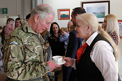 The Prince of Wales, Colonel, Welsh Guards is served a drink by Maggie Cooper as he meets members and family of the 1st Battalion Welsh Guards following their return from Afghanistan, at Elizabeth Barracks, Pirbright Camp in Woking.