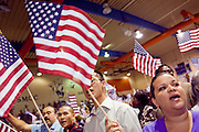 """04 JULY 2009 -- PHOENIX, AZ: VERONICA SOLORIA, originally from Mexico, waves an American flag after becoming a US citizen in Phoenix, July 4. U.S. Citizenship and Immigration Services and South Mountain Community College in Phoenix, AZ, hosted the 21st annual """"Fiesta of Independence"""" Saturday, July 4. More than 180 people from 58 countries took the US Oath of Citizenship and became naturalized US citizens. The ceremony was one of dozens of similar ceremonies held across the US this week. USCIS said more than 6,000 people were naturalized US citizens during the week.  Photo by Jack Kurtz / ZUMA Press"""