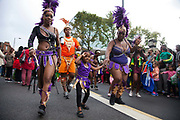 Hackney carnival 2014. The procession started in Ridley Road and passed by the The Hackney Town Hall with thousands of spectators lining the road. A young girl dressed in purple dances along with the adults.