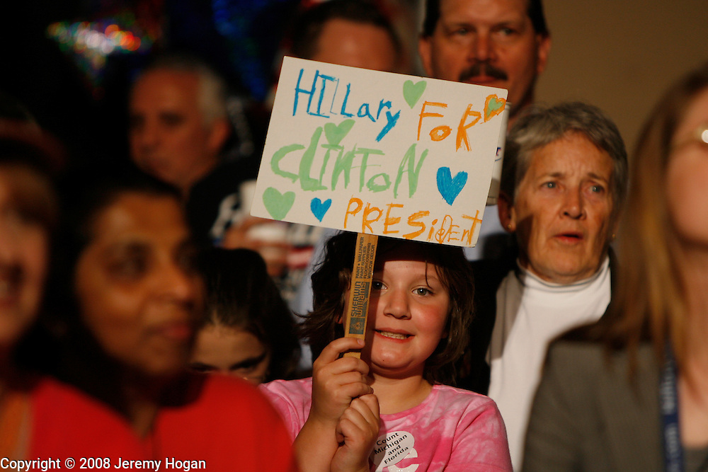 I young Hillary Clinton supporter holds a hand made sign in support.