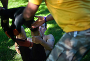 Brad Brenner of Austin, TX watches as volunteers rip the wetsuit off his feet during the transition stage...