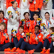 TOKYO, JAPAN August 8:  Five-time Olympic gold medalists Diana Taurasi, (left) and Sue Bird of the United States sit with the Japanese team during a group photograph with their medals after the United States victory during the Japan V USA basketball final for women at the Saitama Super Arena during the Tokyo 2020 Summer Olympic Games on August 8, 2021 in Tokyo, Japan. (Photo by Tim Clayton/Corbis via Getty Images)