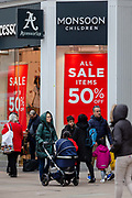 People walk past a branch of Monsoon displaying a 50% off sale sign in Oxford Street, London, UK on January 03, 2019