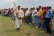 Khui Doloon Khudag, Mongolia, July 2003..Competitors and spectators at the Mongolian Wrestling contests in the national Naadam. Mongolian wrestling champion Usukhbayar displays his trophy to crowds.