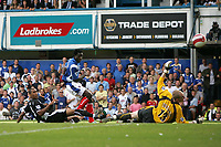 Photo: Lee Earle.<br /> Portsmouth v Wigan Athletic. The Barclays Premiership. 09/09/2006. Portsmouth's Benjani (C) places the ball past Wigan keeper Chris bKirkland.